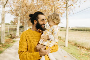 Father carrying his daughter on a morning day in the park in autumn - JRFF02280