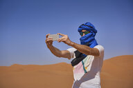 Morocco, man wearing sunglasses and blue tuban taking photo with smartphone in the desert - EPF00515