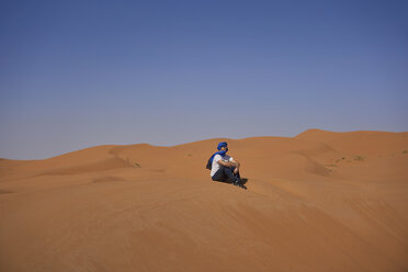 Morocco, man sitting on desert dune looking at view - EPF00518