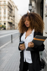 Young woman with laptop bag and coffee to go in the city - MAUF02132