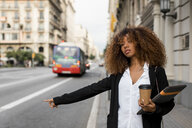 Young woman with laptop bag and coffee to go in the city, hailing a taxi - MAUF02135