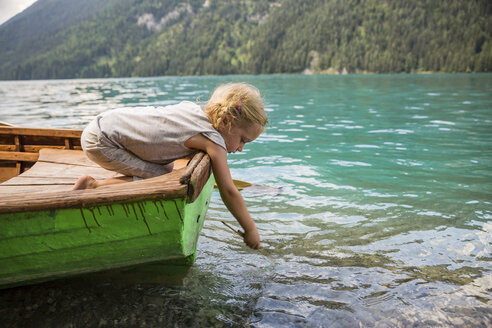 Austria, Carinthia, Weissensee, girl in rowing boat putting a stick in the water - AIF00569