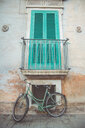 An empty bicycle against a wall of a building - INGF11589