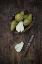 Whole and sliced organic pears 'Conference' with pocket knife on dark wood - LVF07643