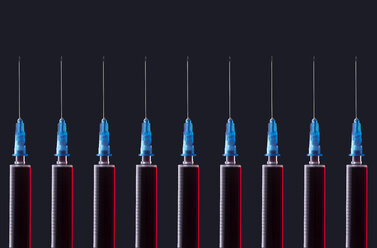 Multiple syringes organized in a pattern over dark background - DRBF00118
