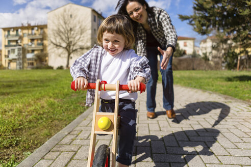 Mother behind happy toddler son with balance bicycle on a path - MGIF00295