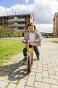 Happy toddler boy with balance bicycle on a path - MGIF00298