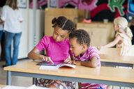 Boy and girl using digital tablet in classroom - ASTF00033