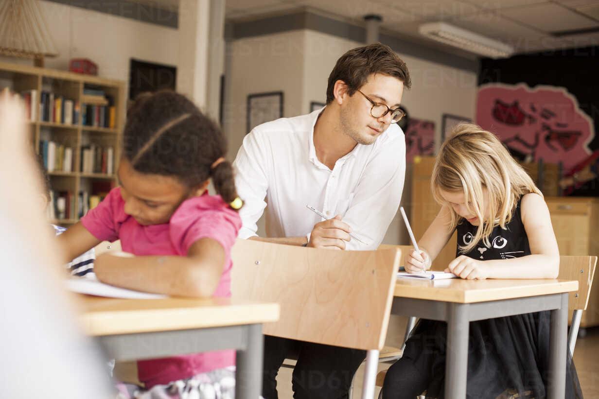 Male teacher teaching girl in classroom - ASTF00045 - Astrakan Images/Westend61