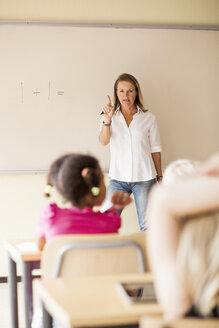 Mature teacher teaching mathematics to children in classroom - ASTF00069