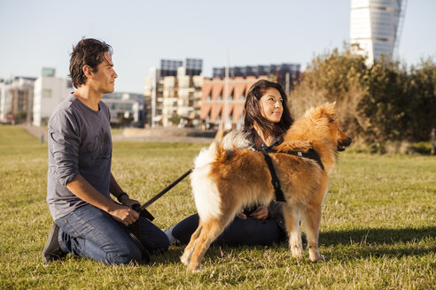 Multi-ethnic couple with dog relaxing at park in city - ASTF00141
