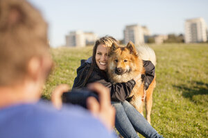 Cropped image of man photographing happy girlfriend embracing dog at park - ASTF00147
