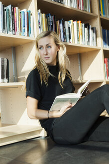 Female student looking away while sitting in college library - ASTF00198