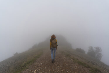 Woman hiking in the fog, walking on a mountain path - AFVF02189
