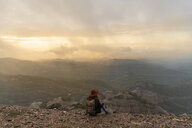 Woman with backback, sitting on mountain, looking at view - AFVF02198