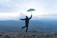 Man jumping for joy on a mountain, holding a green umbrella - AFVF02204