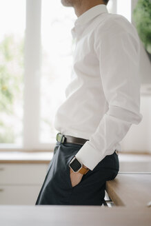 Businessman leaning on kitchen surface with hands in pockets - KNSF05467