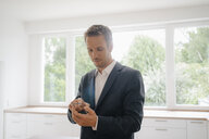 Businessman using glass touch screen in a new home - KNSF05479