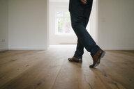Businessman walking in empty flat - KNSF05497