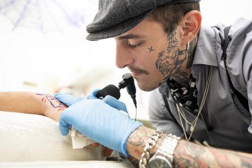 Tattoo artist tattoing hand - DAMF00025