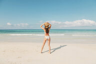 Spain, Mallorca, Rear view of a young woman on holidays standing on the beach - LOTF00001