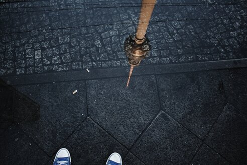 Low section of a person standing on a cobblestone street in Berlin - INGF12024