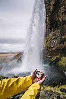 Iceland, Seljalandsfoss Waterfall, woman's hand holding compass - DAMF00033