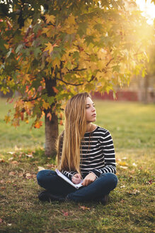 Young woman with notebook sitting on  meadow in a park in autumn taking notes - LOTF00005