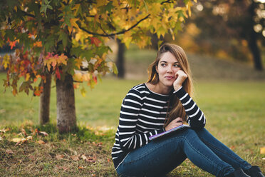 Young blonde woman smiling and holding a notebook in a park. Italy, Emilia-Romagna, Bologna. - LOTF00008