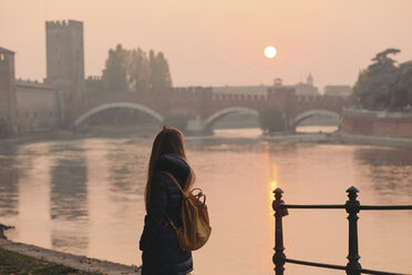 Italy, Verona, back view of woman with backpack looking at view by sunset - LOTF00011