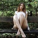 A young woman sitting on a bench in the park - INGF12052