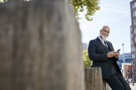 Elegant businessman leaning on wall in the city, using smartphone - RHF02384