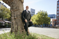 Elegant businessman leaning on tree in the city, thinking - RHF02390