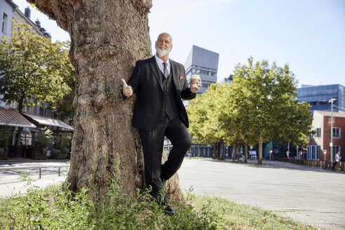 Elegant businessman leaning on tree in the city, drinking coffee - RHF02393