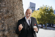 Elegant businessman leaning on tree in the city, holding coffee, screaming for joy - RHF02396