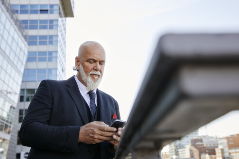 Elegant businessman using smartphone in the city - RHF02402