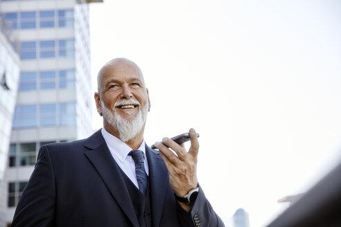 Elegant businessman in the city, using smartphone - RHF02405