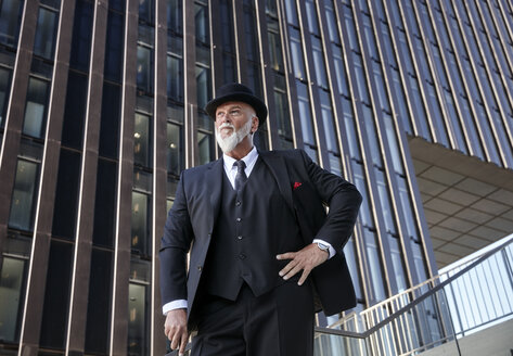 Elegant businessman with bowler hat and walking cane, standing on stairs in the city - RHF02408
