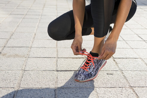 Close-up of young woman tying her shoes before workout - MAUF02148