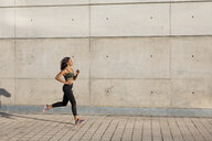 Young woman running along concrete wall in the city - MAUF02151