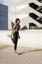 Young woman doing stretching exercise in the city - MAUF02160