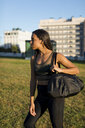 Sporty young woman with bag standing on meadow the city - MAUF02172
