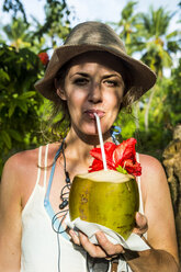Maledives, Ari Atoll, Nalaguraidhoo, Sun Island, portrait of woman drinking fresh coconut water - RUNF00731