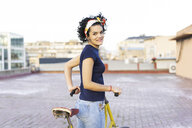 Portrait of smiling young woman with bicycle in the city - ERRF00428