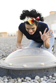Smiling young woman looking through skylight on roof terrace raising her hand - ERRF00440