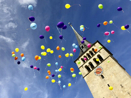 Germany, Sindelfingen, colourful wedding balloons in the sky over church spire - MABF00512