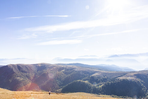 Italy, South Tyrol, Dolomites, Hafling, female hiker on dried mountain meadow in late summer - MMAF00730