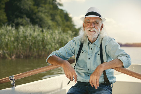 Portrait of senior man sitting in rowing boat on a lake wearing suspenders and summer hat - VWF00018