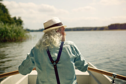 Back view of senior man sitting in rowing boat on a lake wearing suspenders and summer hat - VWF00021