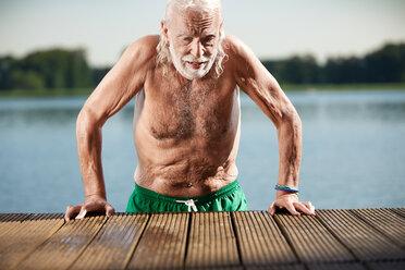 Best Ager Model, alter Mann am See, spritz Wasser aus seinem Mund am Steg. - VWF00024